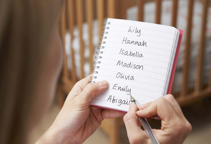 mom writing baby girl names on notepad