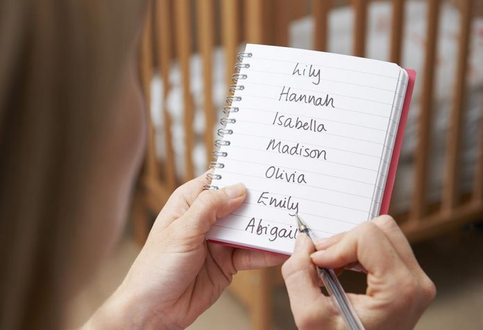 expectant mom writing baby names on notepad