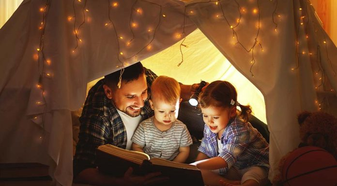 father reading a storybook to his toddlers