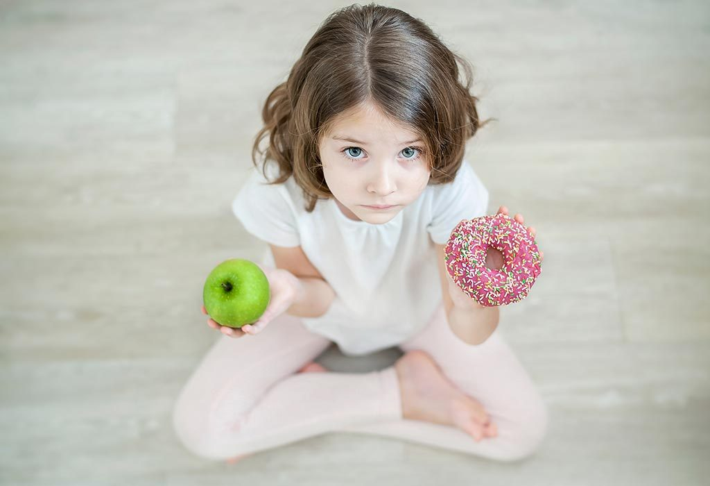 baby confused between a fruit and a doughnut