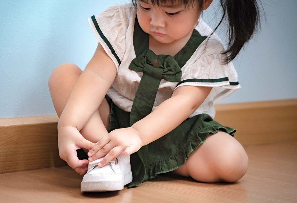child putting on her shoes