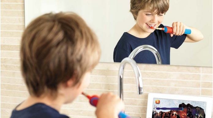 Boy brushing teeth with Orab B electric toothbrush