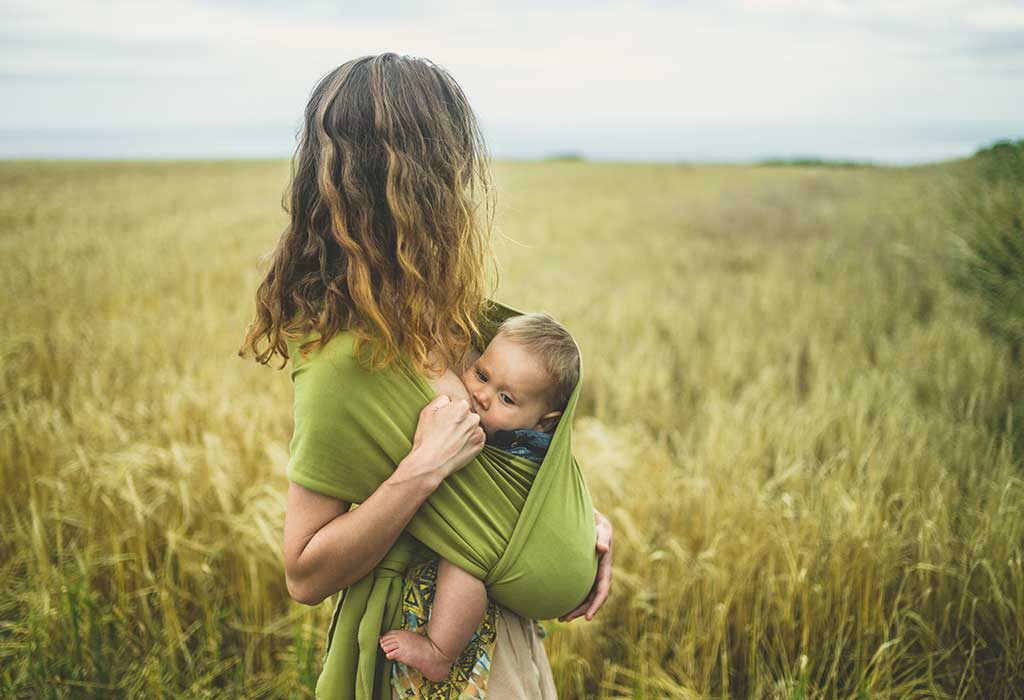 mom feeding baby while carrying her in a baby carrier