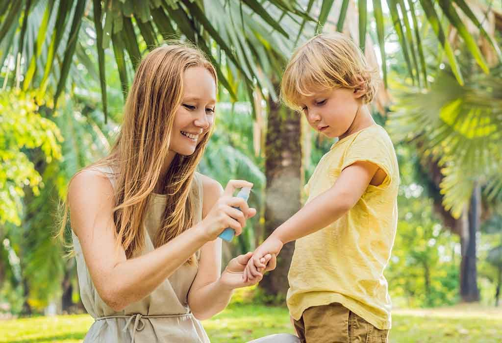 A mother spraying a bug repellent on her child's arms