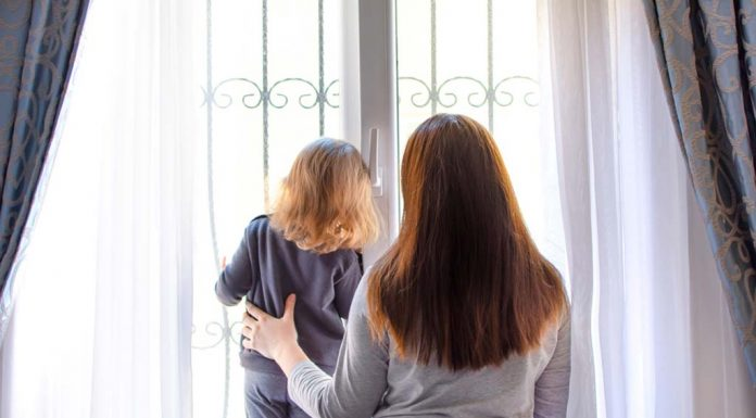 homebound mom and daughter watching out the window