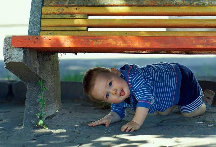 mischievous toddler under a bench