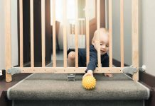 baby picking her ball through a baby safety gate