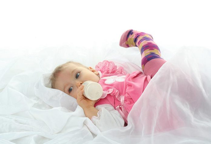 baby drinking from a feeding bottle